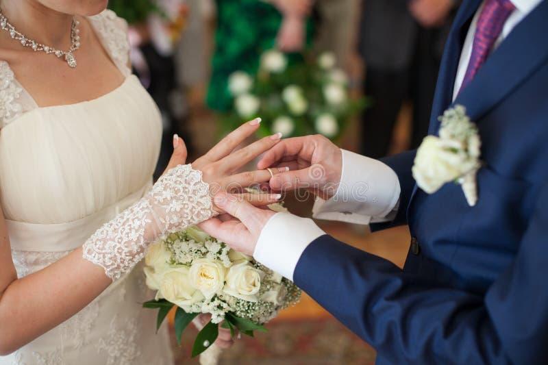Den nygift personbruden och brudgummen som utbyter guldbröllopcirklar på, cere arkivbilder