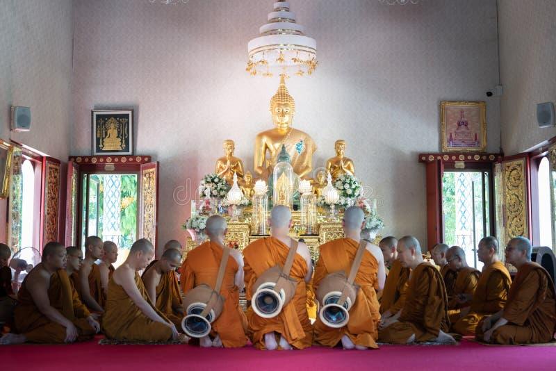 Den nyligen förordnade buddistiska munken ber med prästprocessionen royaltyfria foton