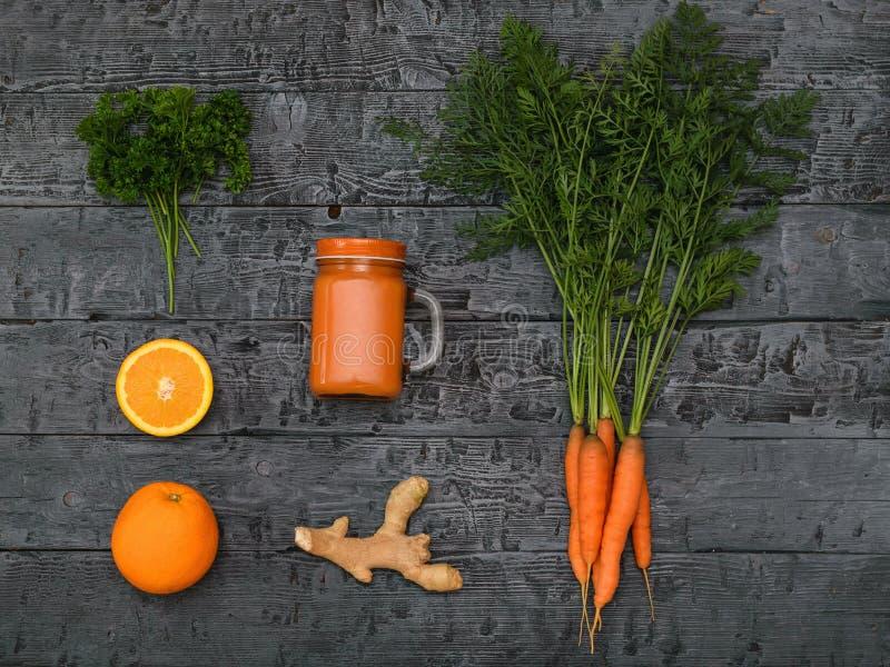 Den nytt gjorda morotsmoothien, gruppen av morötter, apelsinen och ingefäran rotar på en lantlig tabell övre sikt Lekmanna- lägen arkivbild