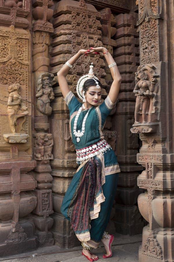 Den Odissi dansaren bär den traditionella dräkten och utför den Odissi dansen på den Mukteshvara templet, Bhubaneswar, Odisha, In arkivfoto