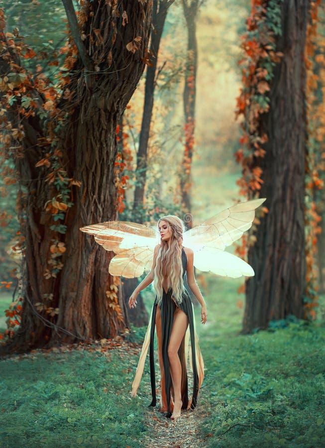 Den oerhörda fen går i höstskogen en blond flicka med mycket långt hår, ovanligt utforma Älva i en grön klänning arkivbild