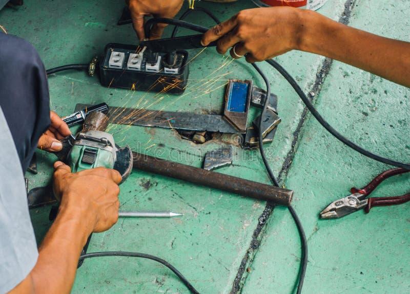 Den oförsiktiga arbetarbrukshanden som maler utan säkerhetshandskar, uttag som frambringar elektricitet, gristrar royaltyfria foton