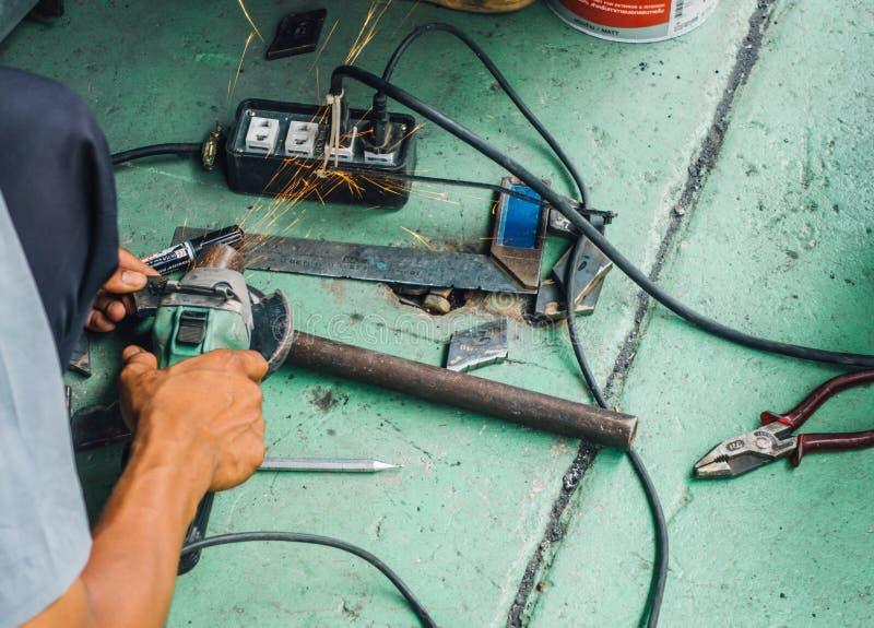 Den oförsiktiga arbetarbrukshanden som maler utan säkerhetshandskar, uttag som frambringar elektricitet, gristrar royaltyfri foto
