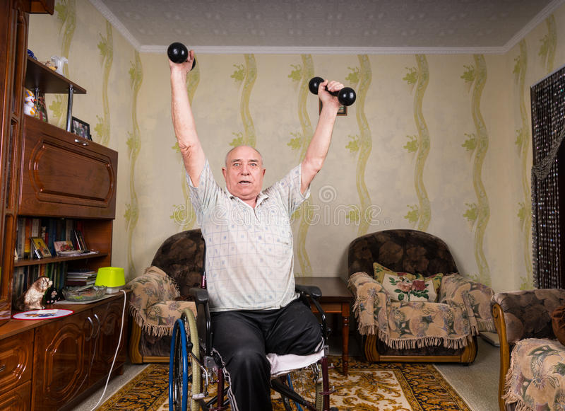 Den ogiltiga gamala mannen sätter upp hans händer med hantlar fotografering för bildbyråer