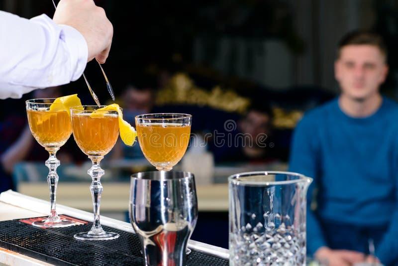 Den oidentifierade bartendern som förbereder coctailen på stångräknaren, ska göra det royaltyfri fotografi