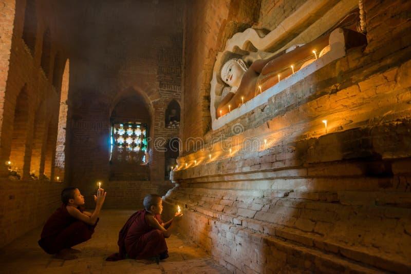 Den oidentifierade buddismneofyt ber i den Buddihist templet fotografering för bildbyråer