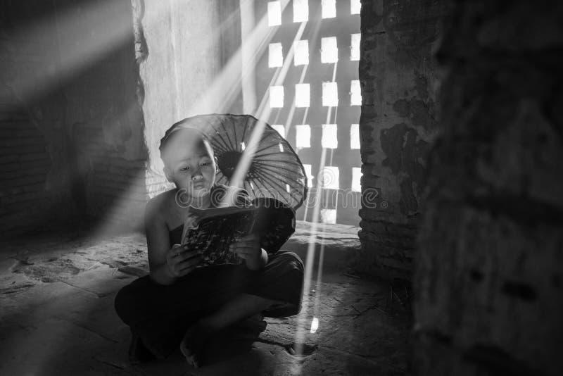 Den oidentifierade buddismneofyt läste en bok i den Buddihist templet arkivfoton