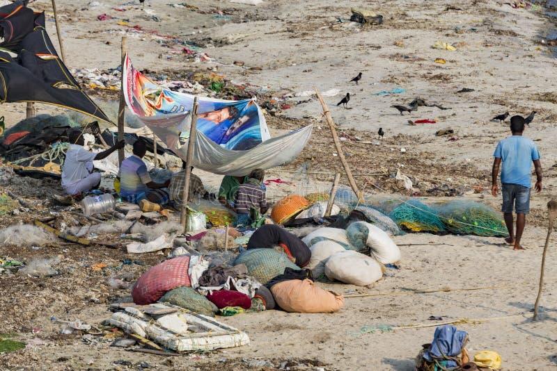 Den oidentifierade fattiga lokala traditionella fiskaren bor på stranden i mitt av avskrädet och korna och getterna, under tält arkivbild