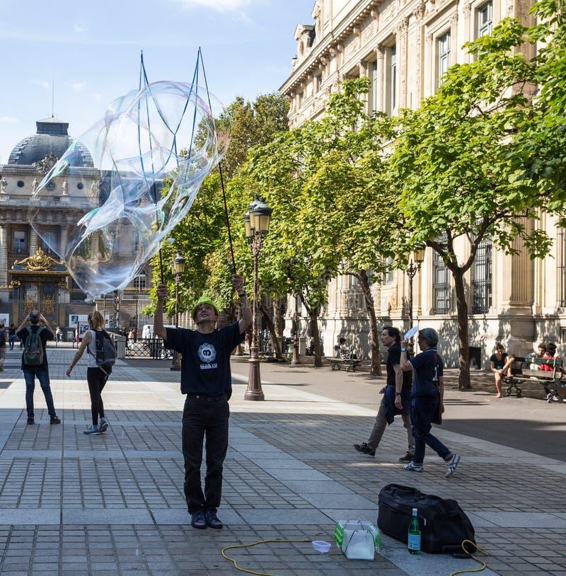 Den oidentifierade gatakonstnären blåser enorma färgrika såpbubblor i Paris på September 9, 2018 arkivfoton