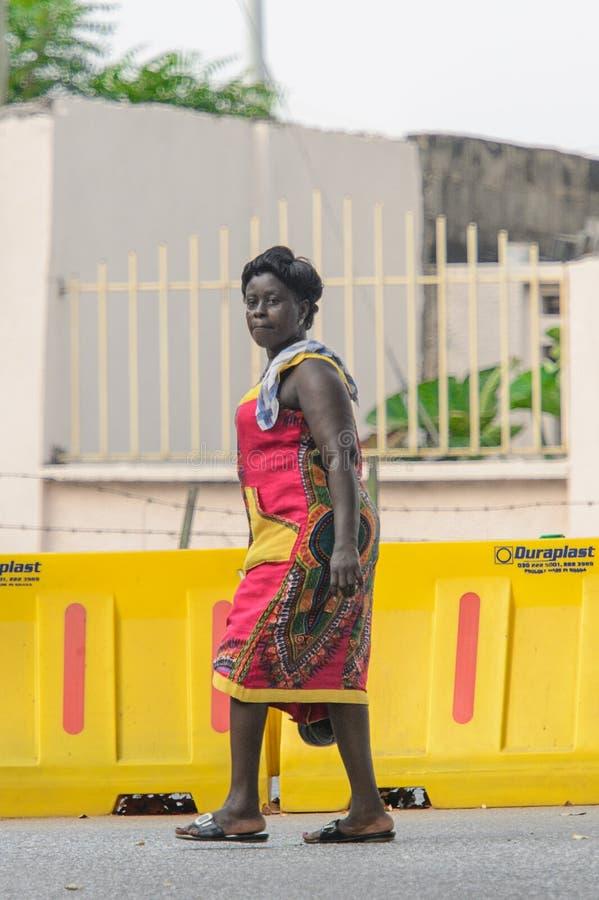 Den oidentifierade ghananska kvinnan går över gul fäktning royaltyfria bilder