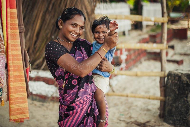 Den oidentifierade indiska kvinnan och att behandla som ett barn i hennes armar ler med mycket royaltyfri fotografi