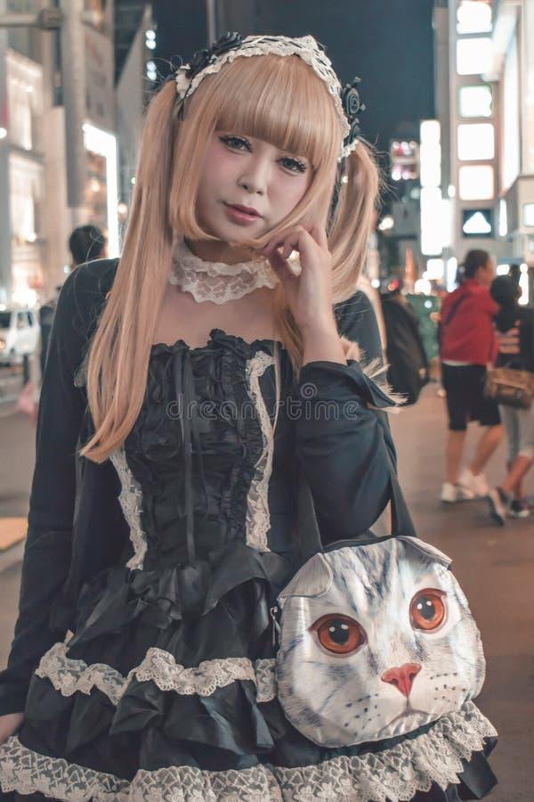 Den oidentifierade japanska flickan med blondinen dök hår med a katt-som handväskan på Harajuku i det Tokyo Japan exemplet av royaltyfri bild