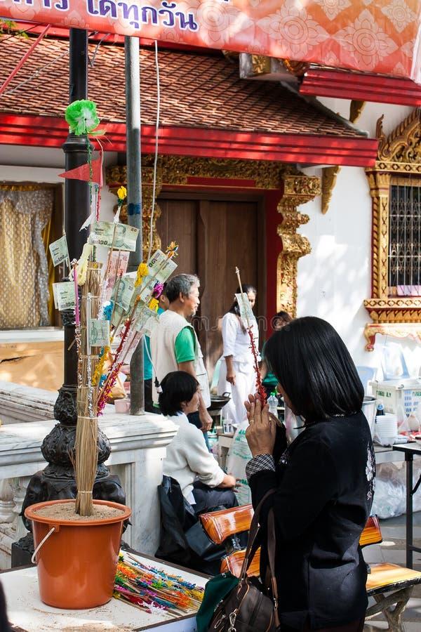 Den oidentifierade kvinnan donerar pengar och ber för att göra meriter royaltyfri fotografi