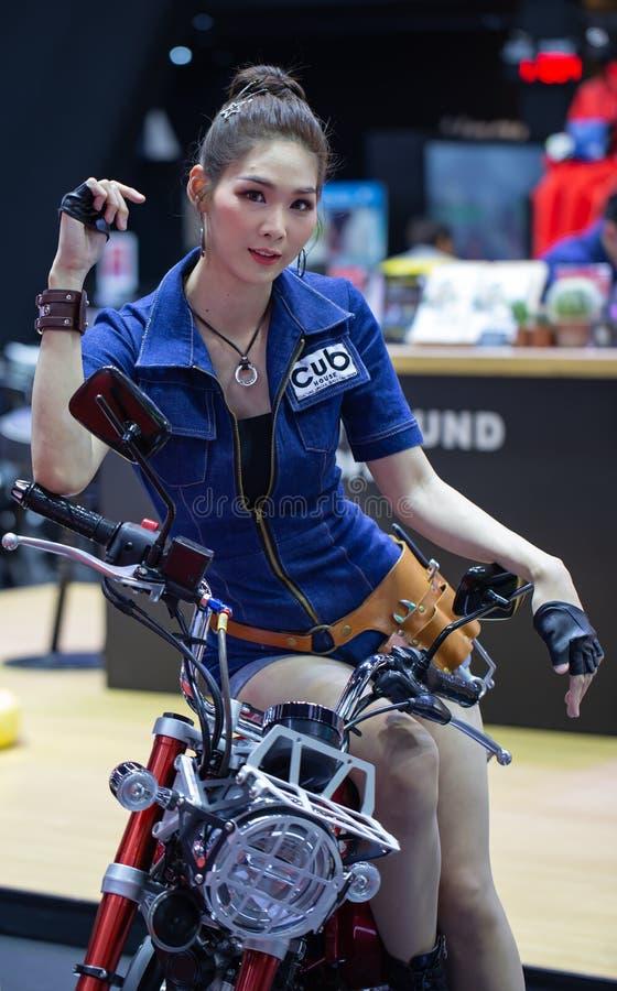 Den oidentifierade kvinnliga presentatören poserar med den retro motorcykeln för den Honda gröngölingen royaltyfri bild