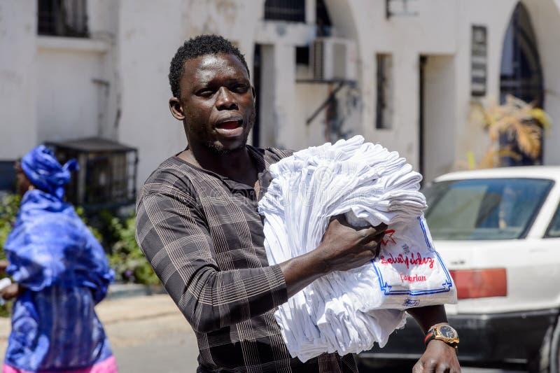 Den oidentifierade senegalesiska mannen promenerar gatan med gods f royaltyfria foton