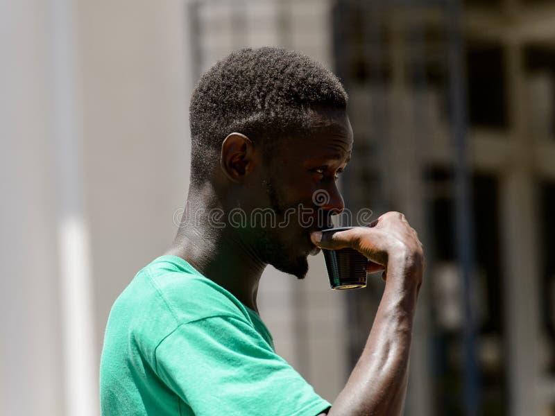 Den oidentifierade senegalesiska mannen rymmer en plast- kopp i mittnollan arkivfoto
