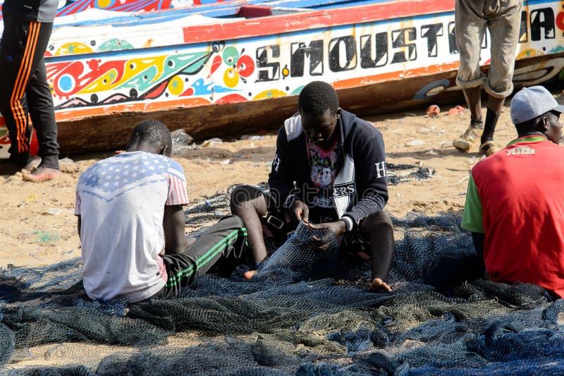 Den oidentifierade senegalesiska mannen syr ett fisknät på kusten av arkivfoton