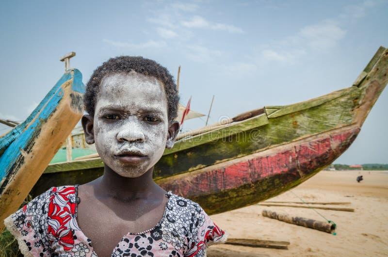 Den oidentifierade unga afrikanska flickan med vit målade framsidan på stranden framme av färgrika fiskebåtar royaltyfria bilder