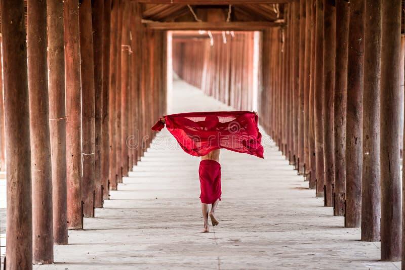 Den oidentifierade unga buddismnovisen spelar i träpoler t arkivbilder
