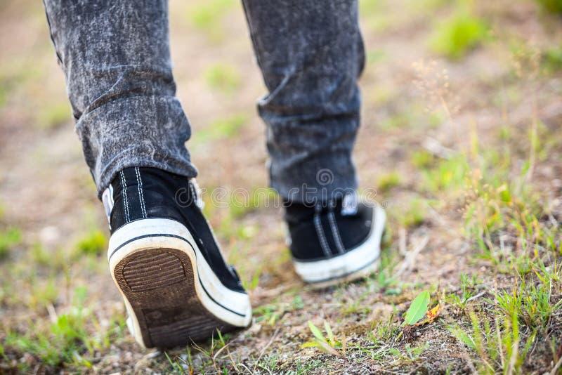 Den oigenkännliga mannen i gummi skor att kliva på vandringsledet, den bakre sikten, closeup royaltyfri fotografi