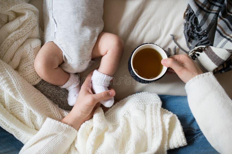 Den oigenkännliga modern med nyfött behandla som ett barn sonen som ligger på säng royaltyfri bild