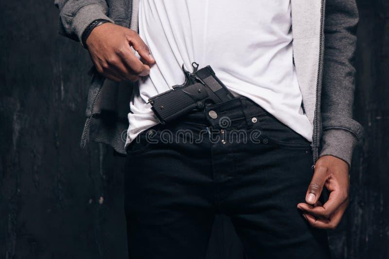 Den oigenkännliga svarta mannen hotar med ett vapen royaltyfria bilder