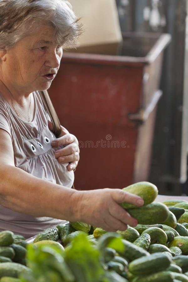 Den okända äldre kvinnan köper gurkor på marknaden arkivfoto
