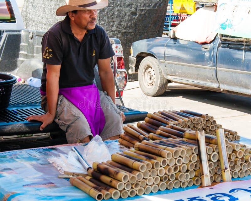 Den okända gatuförsäljaren av klibbiga ris i bambu fogar ihop nära den berömda Maeklong järnväg marknaden royaltyfri foto