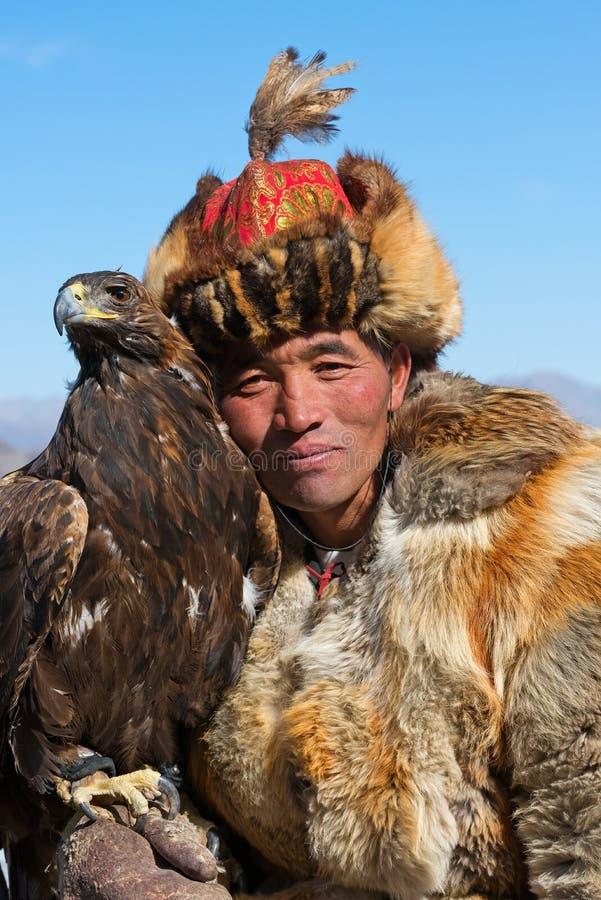 Den okända huntsmanen visar hans guld- Eagle som utbildas för falkenerarkonst royaltyfri foto