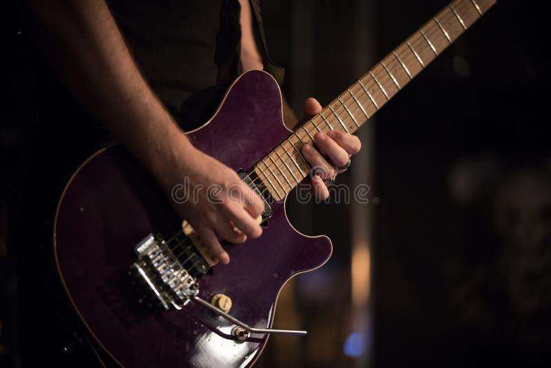 Den okända musikern spelar gitarren i jazzstången, levande kapacitet arkivbilder