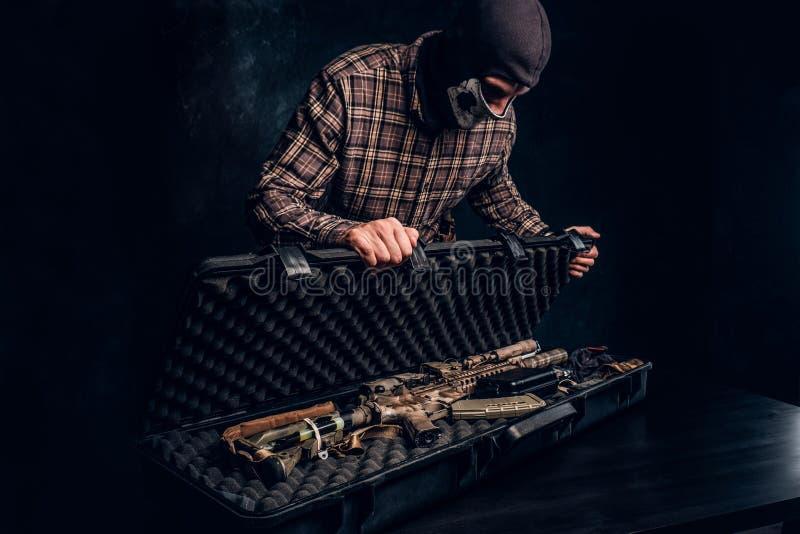 Den olagliga f?rs?ljningen av vapen, svart marknad, brottslingen ?ppnar fallet med ett anfallgev?r och visar det till k?paren arkivbilder