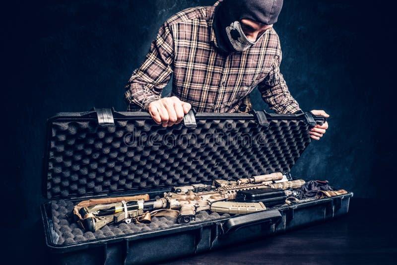 Den olagliga f?rs?ljningen av vapen, svart marknad, brottslingen ?ppnar fallet med ett anfallgev?r och visar det till k?paren royaltyfri foto