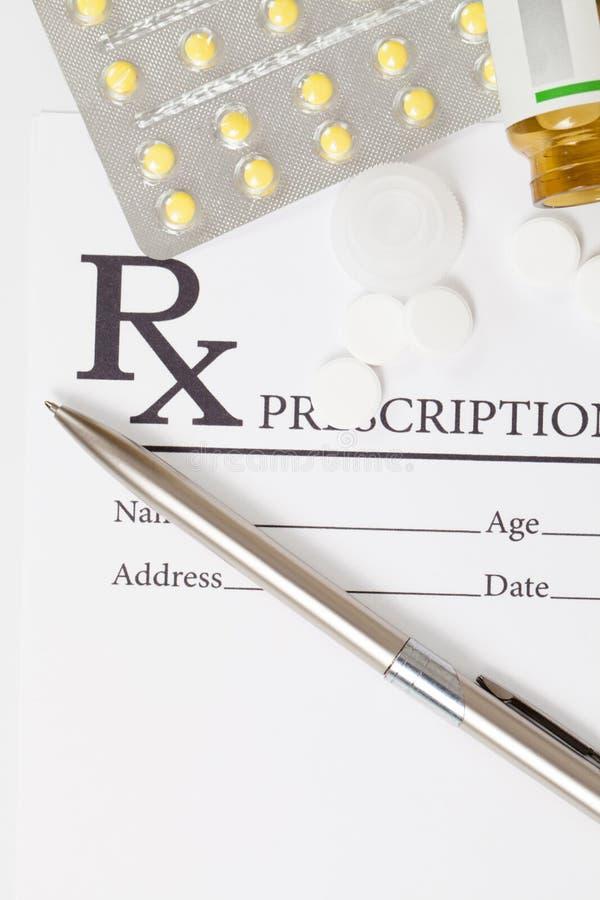 Den olika preventivpillerar och silverfärgpennan över medicinskt recept bildar royaltyfri foto