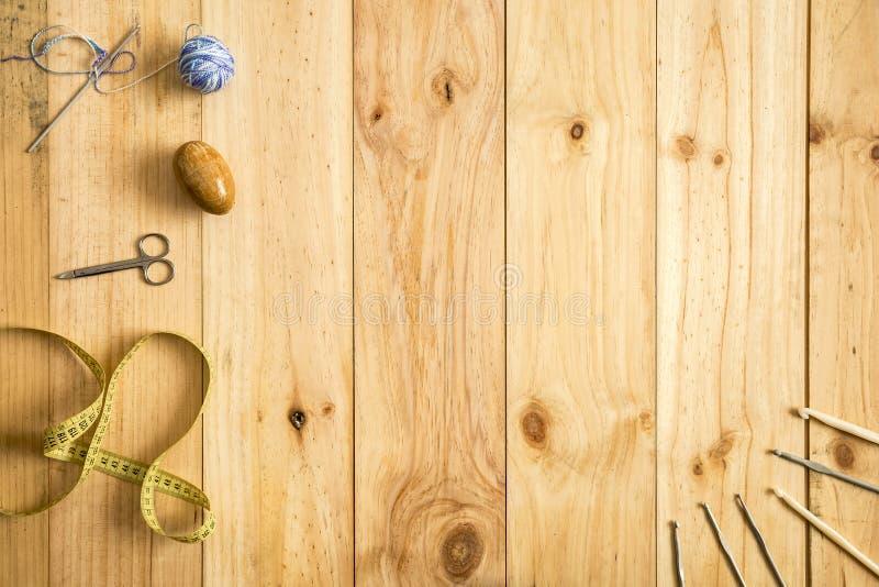 Den olika sömnaden bearbetar, inklusive sax, måttband, ulltrådar och visare på ljus wood bakgrund arkivbild