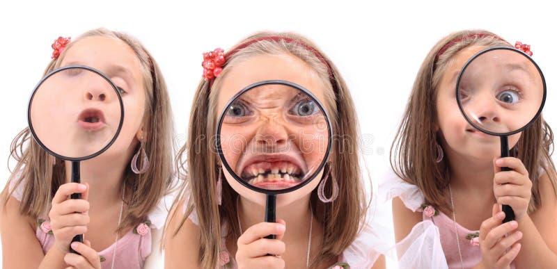 Den olika söta lilla flickan vänder mot (leendet, ögat, tandläkareframsidor) royaltyfri bild