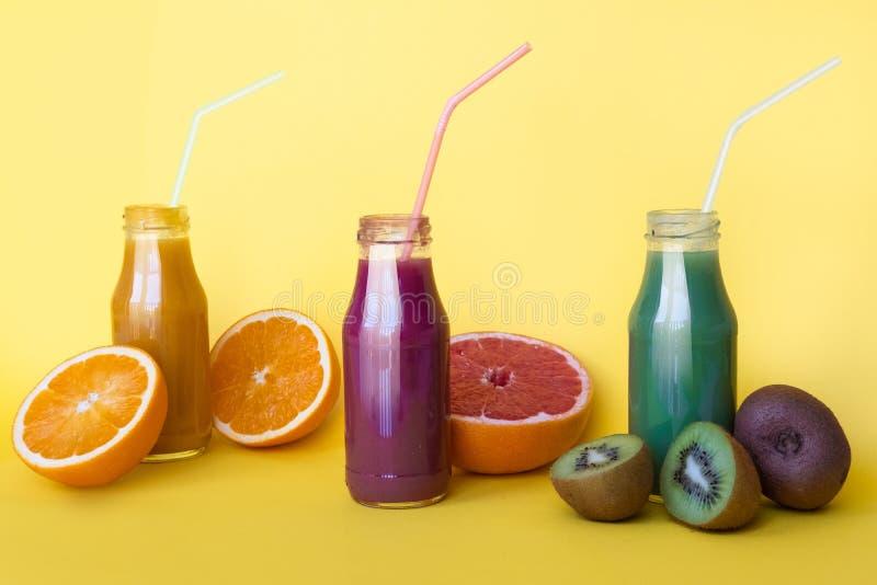 Den olika sorten av smoothies eller fruktsafter i flaskor som är sund bantar matbegrepp på guling fotografering för bildbyråer