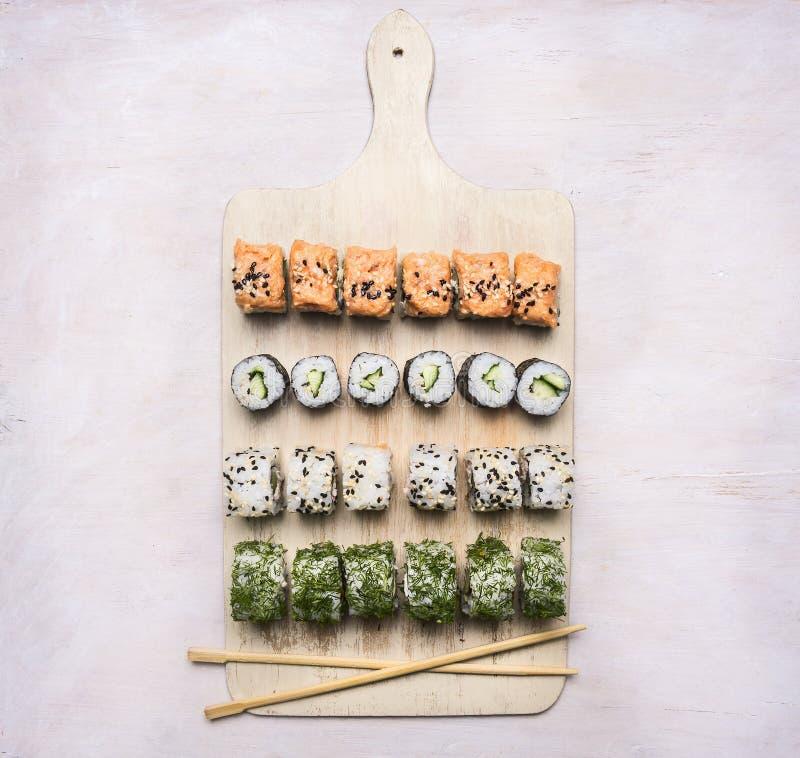 Den olika sushi ställer, dill, laxen, krabba på en asiatisk mat för vit skärbräda på trälantligt slut för bästa sikt för bakgrund royaltyfria foton