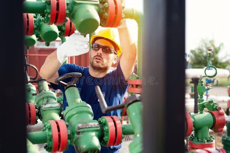 Den olje- arbetaren kontrollerar den olje- pumpen på solnedgångbakgrunden royaltyfria bilder
