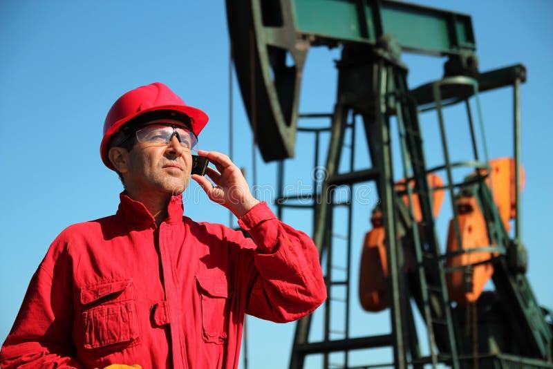 Den olje- arbetaren som använder cellen, ringer bredvid Pumpjack royaltyfri bild