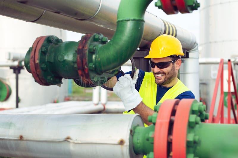 Den olje- arbetaren stänger ventilen på den olje- rörledningen royaltyfri fotografi