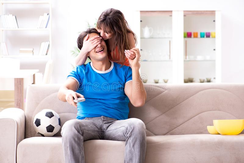 Den olyckliga frun som maken håller ögonen på fotboll fotografering för bildbyråer