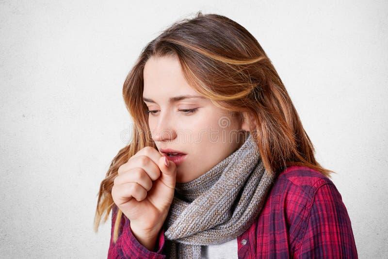 Den olyckliga kvinnlign hostar, som fångad förkylning på frostigt väder, bär den varma halsduken på hals, har thorehalsen som iso royaltyfri fotografi
