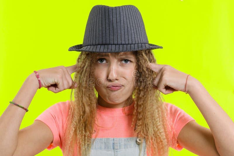 Den olyckliga tonåriga flickan täckte hennes öron, över gul studiobakgrund fotografering för bildbyråer