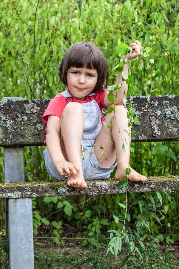 Den olyckliga ungen som bara spelar med murgrönan, lämnar att skrapa den kala foten royaltyfri foto