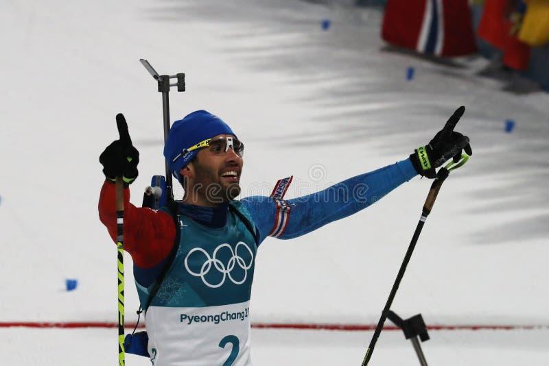Den olympiska mästaren Martin Fourcade av Frankrike firar seger i start för mass för biathlonman` s 15km på de 2018 vinterOS:erna royaltyfri bild