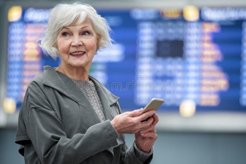 Den optimistiska gråhåriga damen är le och rymma smartphonen arkivbild