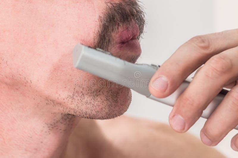 Den orakade mannen klipper hans mustasch med en manuell beskärare utan trådar Slapp fokus Närbild royaltyfri fotografi