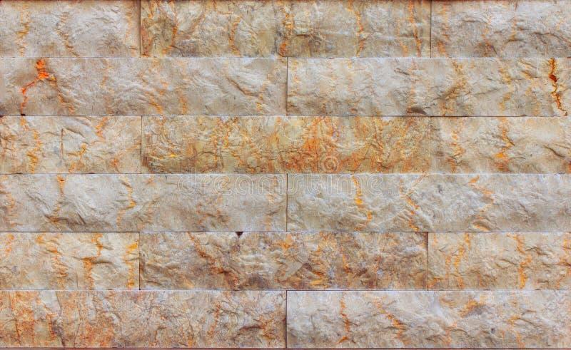 Den orange fasadbeklädnadstenen, kritiserar, sandsten- och travertinemarmortextur royaltyfri bild