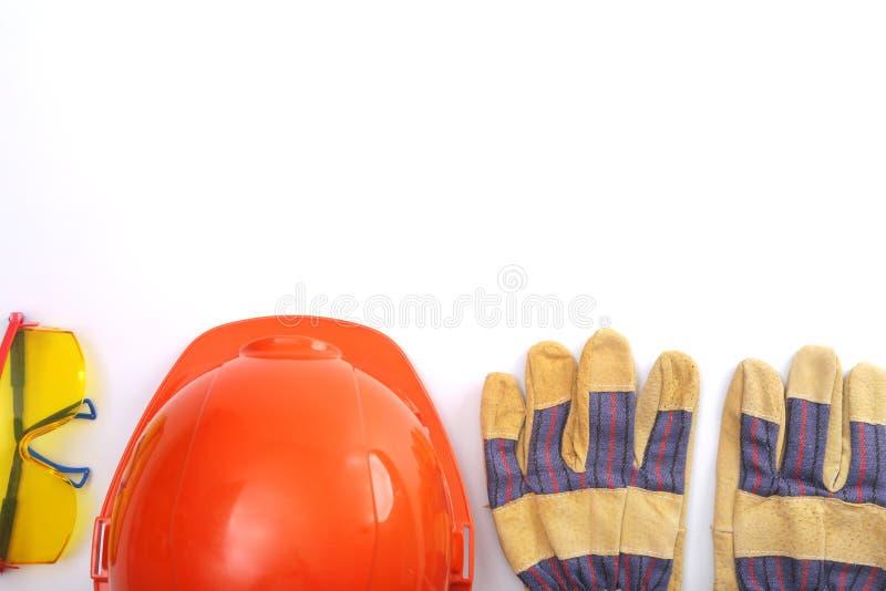 Den orange hårda hatten, piskar arbetshandskar och säkerhetsexponeringsglas på en vit bakgrund kopiera avstånd arkivbilder