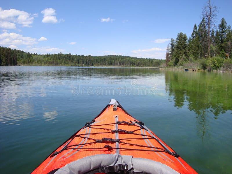 Den orange kajaken svävar på British Columbia sjön royaltyfri bild